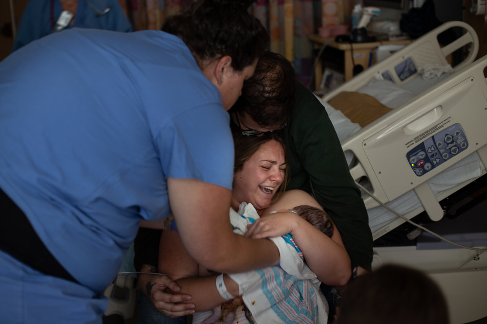 Woman holds her baby for the first time in a hospital birth.