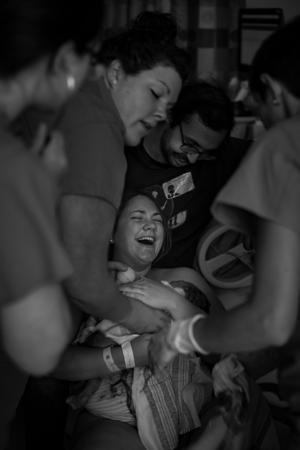 New mom is surprised and overjoyed as she holds her newborn bay.