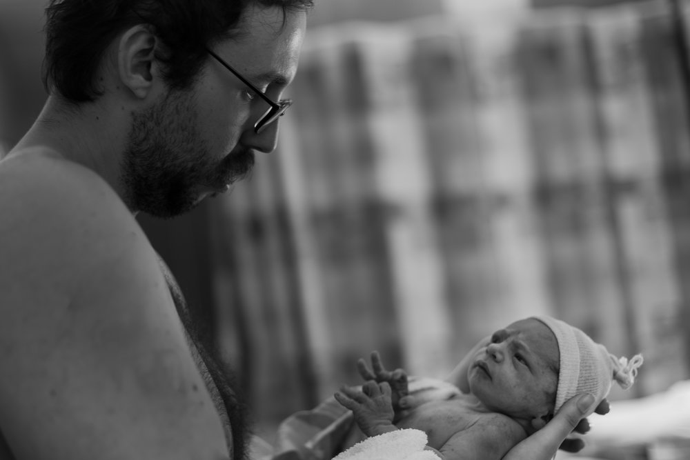 black and white photo of a man holding his newborn baby.