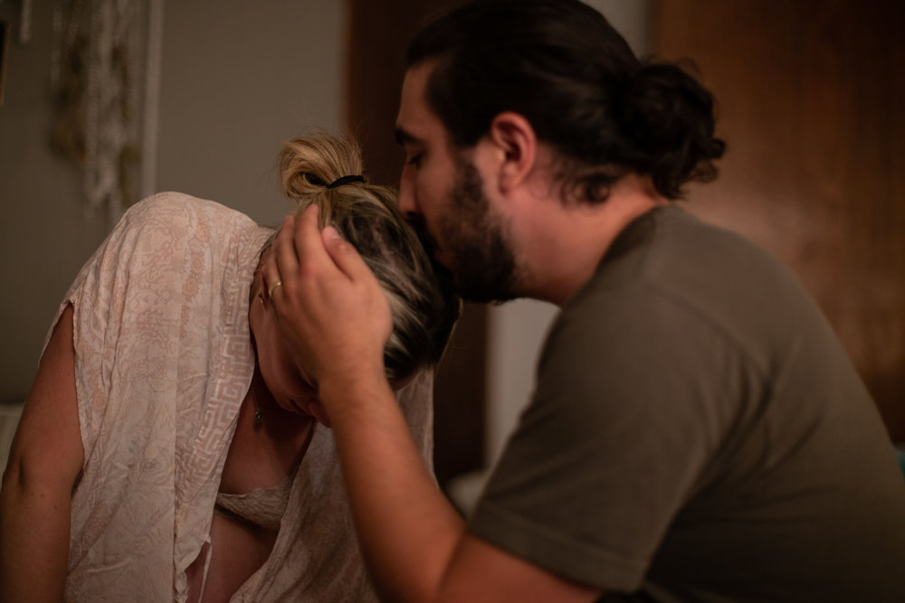 Husband kissing his wife on the top of her head while she is in labor.