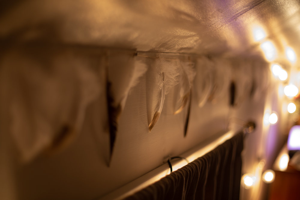 Feathers lit by christmas lights on the wall during a homebirth.