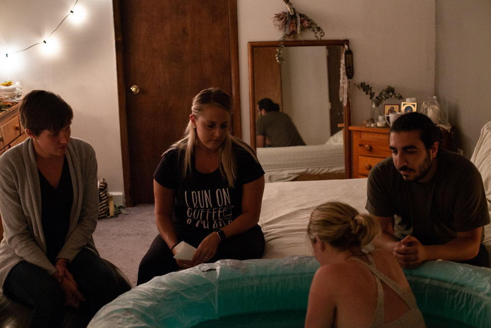 A laboring woman with her husband, midwife and nurse surrounding her in a birth pool during her home birth.