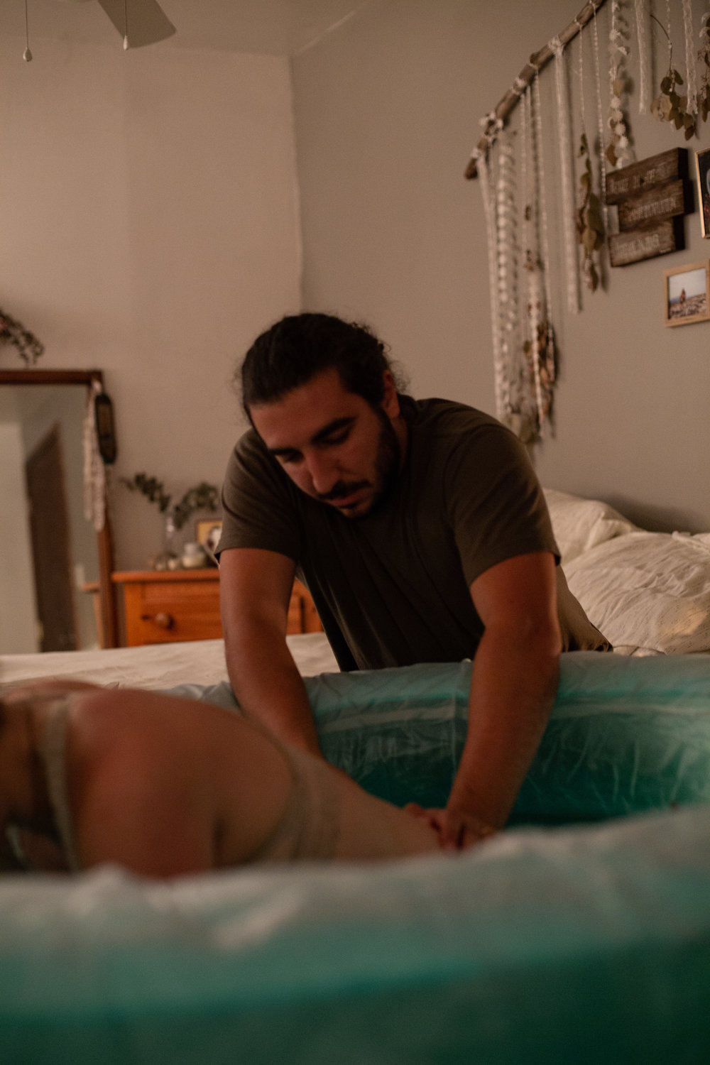 A man giving counter pressure to his wife during labor in their Buffalo home birth.