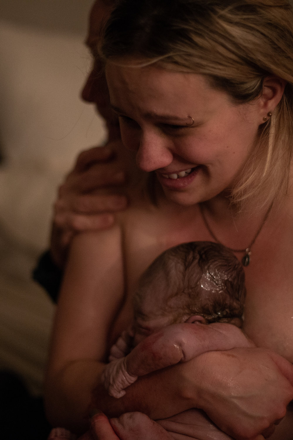 A new mother holds her baby for the first time and smiles widely.