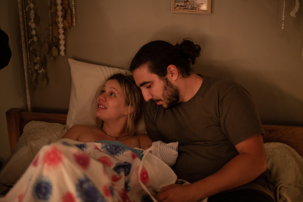 A new mom and dad snuggle with their baby in bed immediately after their home birth.