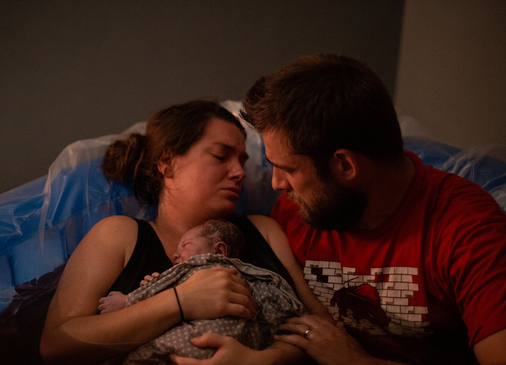 A new mom and dad hold their baby in a birth pool.