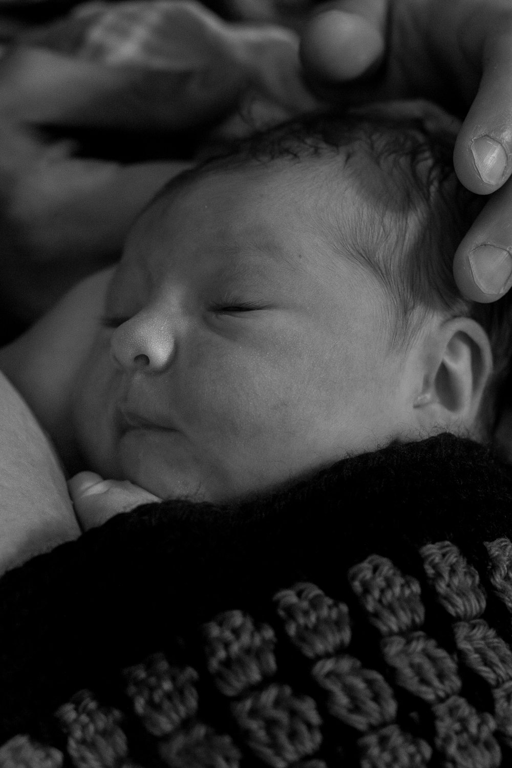 Black and white image of a newborn covered in a hand crocheted blanket.