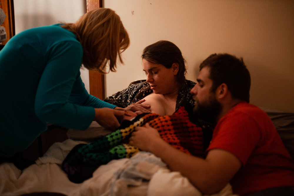 A midwife assistant helped a newborn latch onto the breast during a home birth.
