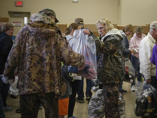 Julie Bustad of Austin, Minnesota, holds up a bag of socks to her husband, Mike, as they shop during the annual Fox River sock sale on Friday, Oct. 6, 2017, in Osage. (Photo: Bryon Houlgrave/The Register)