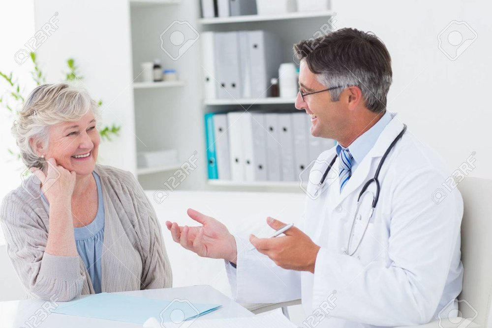 36413529-happy-male-doctor-discussing-with-senior-patient-at-table-in-clinic.jpg