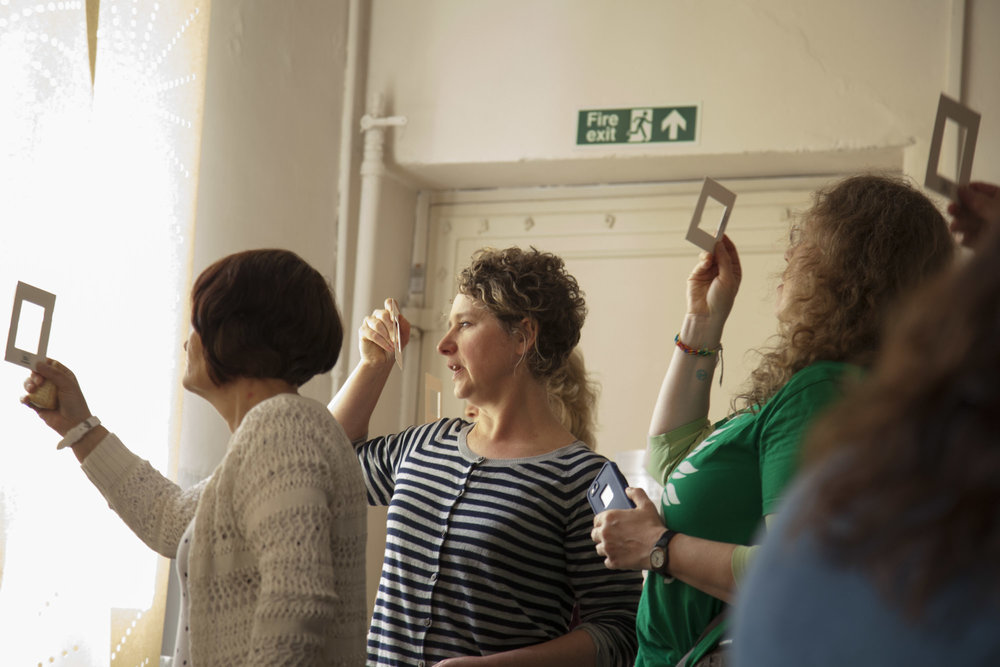 ruth davey professional photography guiding a group to hold photo mounts and look again during a mindfulness photography talk