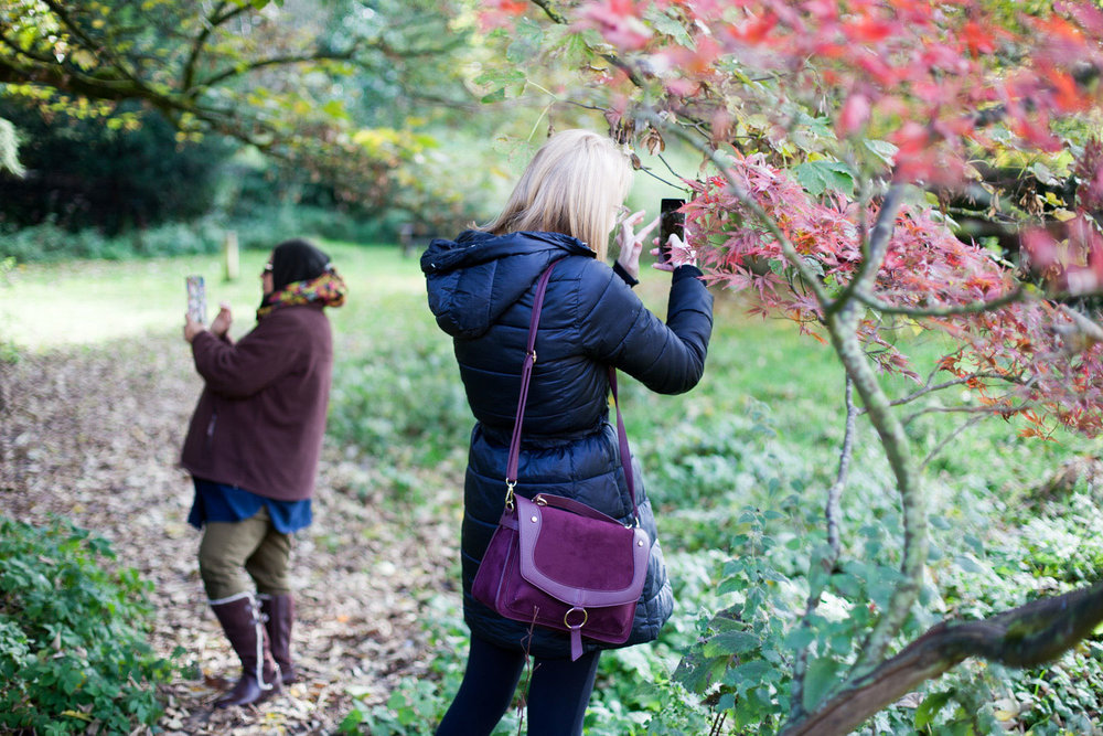 two ladies taking photo in woodlands during mindfulness photography workshop Gloucestershire