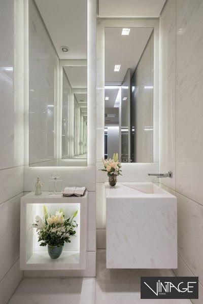 Espelho prata lapidado colado sobre estrutura de alumínio afastada da parede, com iluminação lateral