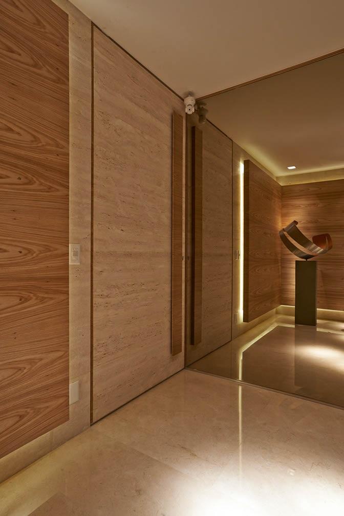 Parede de hall de entrada revestida em espelho bronze e rodapé em perfil inox