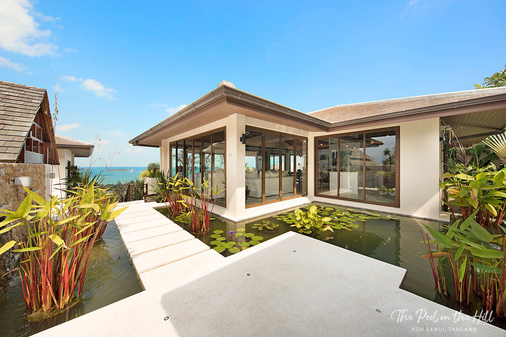 Rent a villa in Thailand: Your arrival at The Pool on the Hill features tropical Thai plants, a large pond, and ocean views across Koh Samui