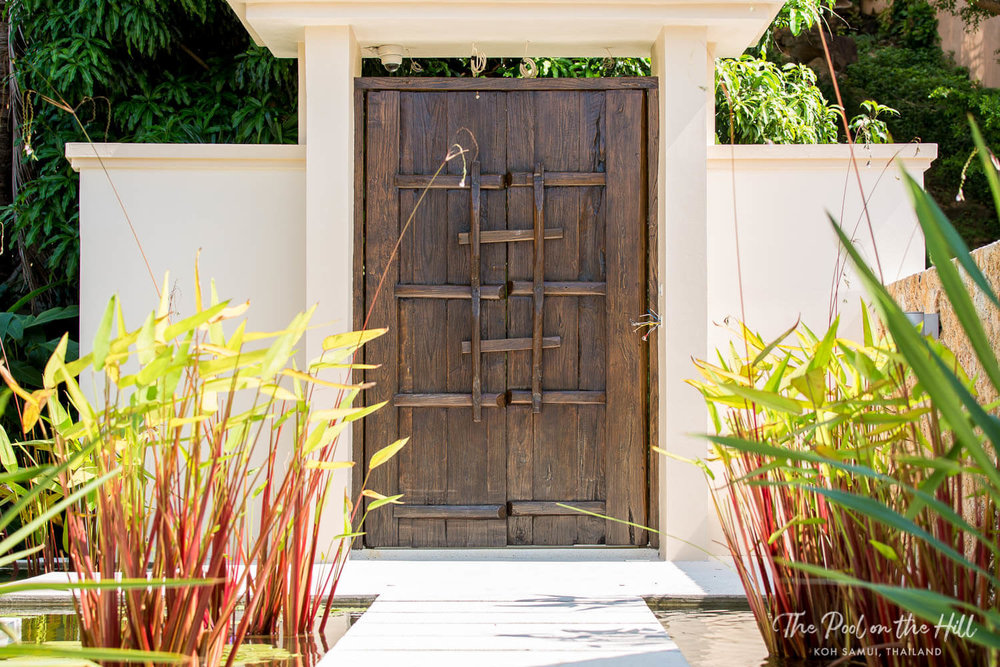 Villa entrance: The antique gates and pond entrance to The Pool on the Hill, a Thai villa in Koh Samui