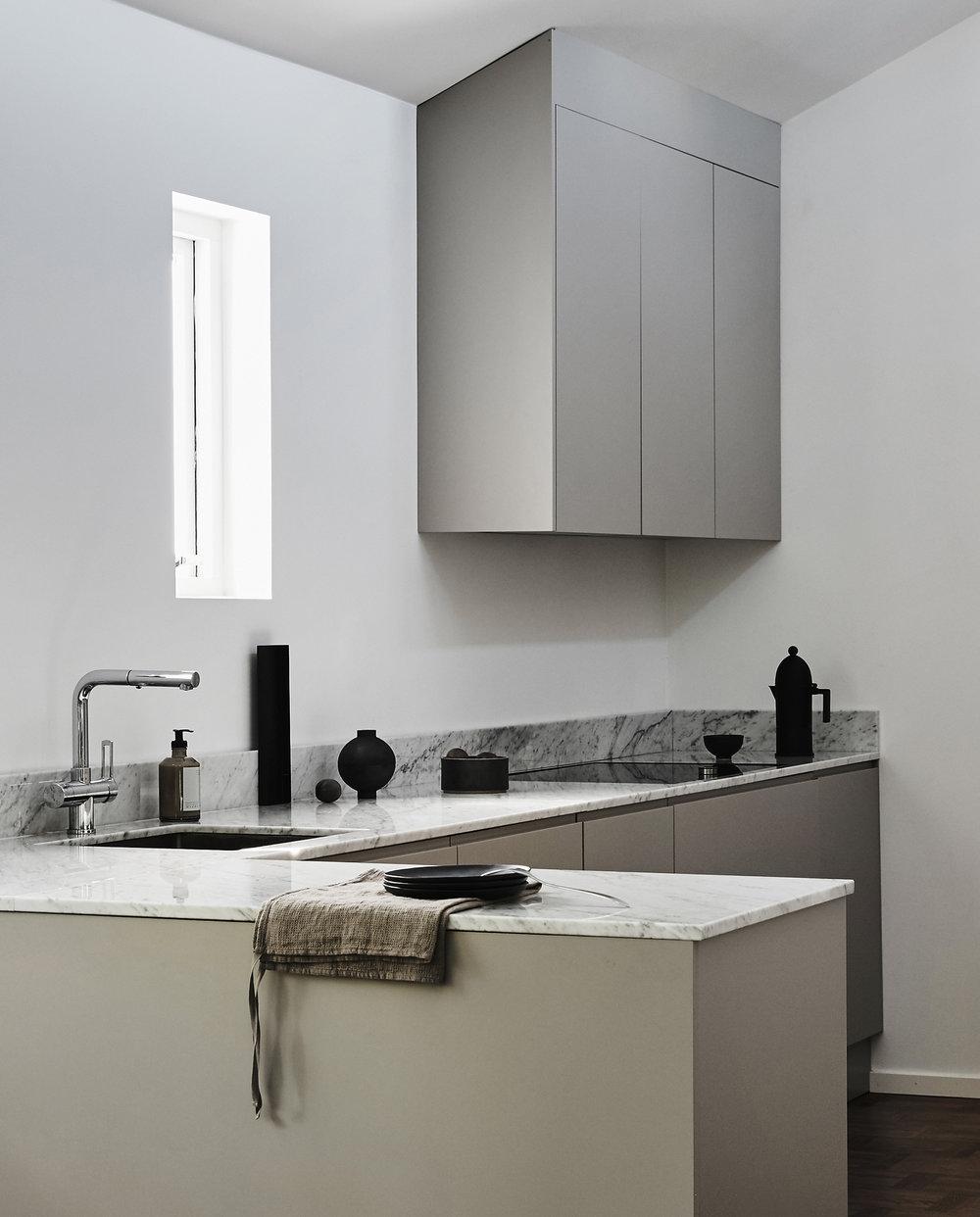 Proffskök med högt i tak där form och funktion går hand i hand. Den mjuka kulören i greige bryter fint mot bänkskivan i marmor. 5 + 1,5m kök. Pris 72.000 sek(Pris exklusive bänkskiva och vitvaror) Se fler bilder