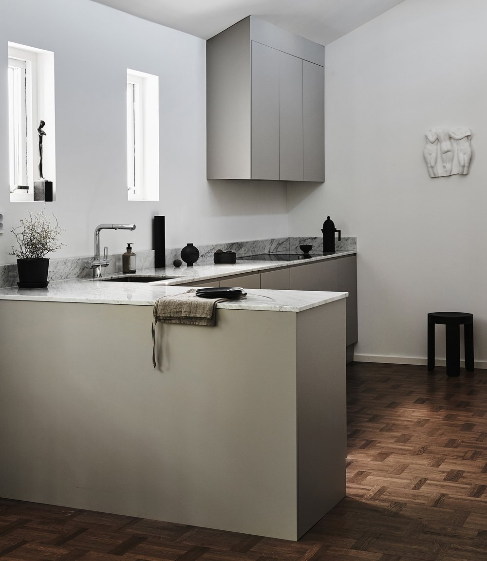 Clean and elegant kitchen ideal for high ceilings where form and function go hand in hand. The soft greige tones set off the marble worktop. Wall cupboards are angled to become one with the space. 5 + 1.5m kitchen.   Price on request     See more pictures