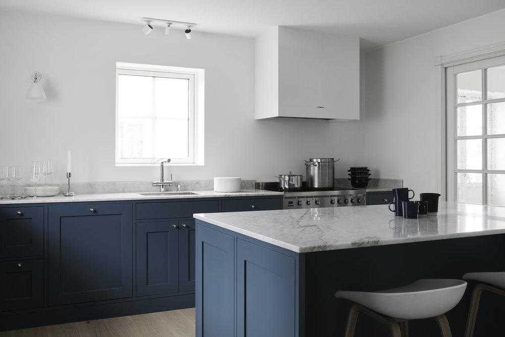 Ett modernt Shakerkök byggt i klassiskt manér med innanförliggande luckor och speglar i alla dörrar och lådfronter. Den dovt gråblå färgen tillsammans med de vita, kala väggarna och de industriella inslagen får köket en modern ton som en kontrast till det rustika och traditionella.Kyl och frys infällt i väggen. Bänkskiva i matt vit Carraramarmor och vitvaror från Smeg.   Prisexempel i grundutförande ca 98.000 - 118.000 sek   Se fler bilder
