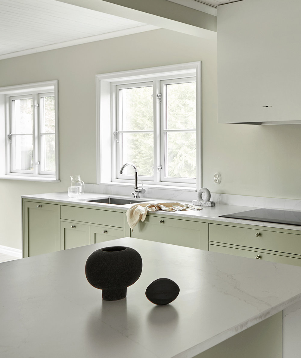 "Clean, minimalist shapes, cabinets and drawers in light ash, together with the pale green color ""Lindblomsgrön"" creates a harmonious balance in this timeless frame kitchen, designed and built by Nordiska Kök. the ""Box"" fan from Fjäråskupan, other appliances from Smeg.   Price on request     See more pictures"