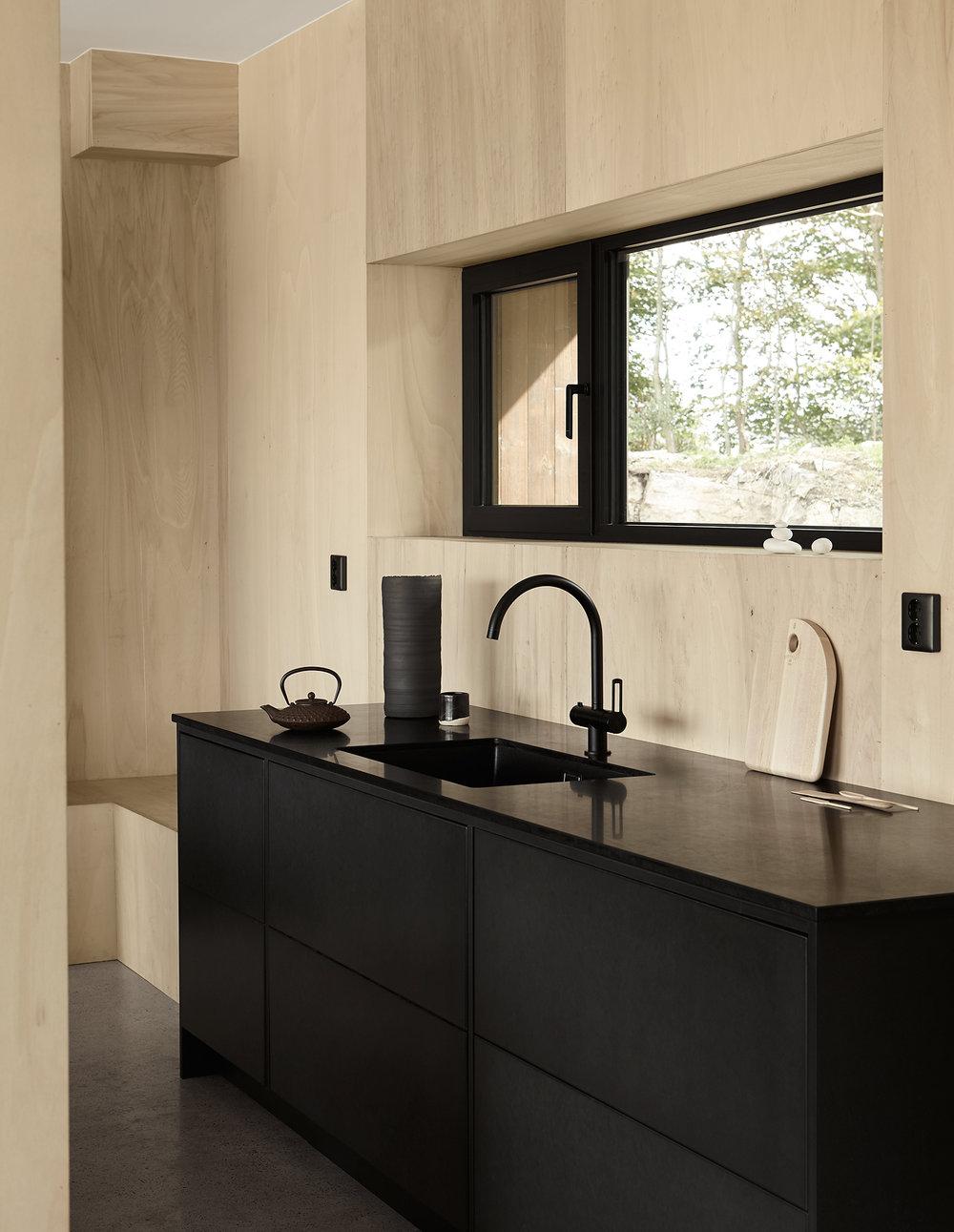Vi har tillsammans med konstnären Emma Bernhard skapat detta svarta valchromatkök till hennes hem i Torekov. En svart, matt granitbänkskiva tillsammans med de svarta detaljerna skapar en kontrast till väggarnas varma trätoner. De tre kökssektionerna blir rummets mitt och ger en unik och minimalistisk köksmiljö.   Pris på förfrågan    Se fler bilder