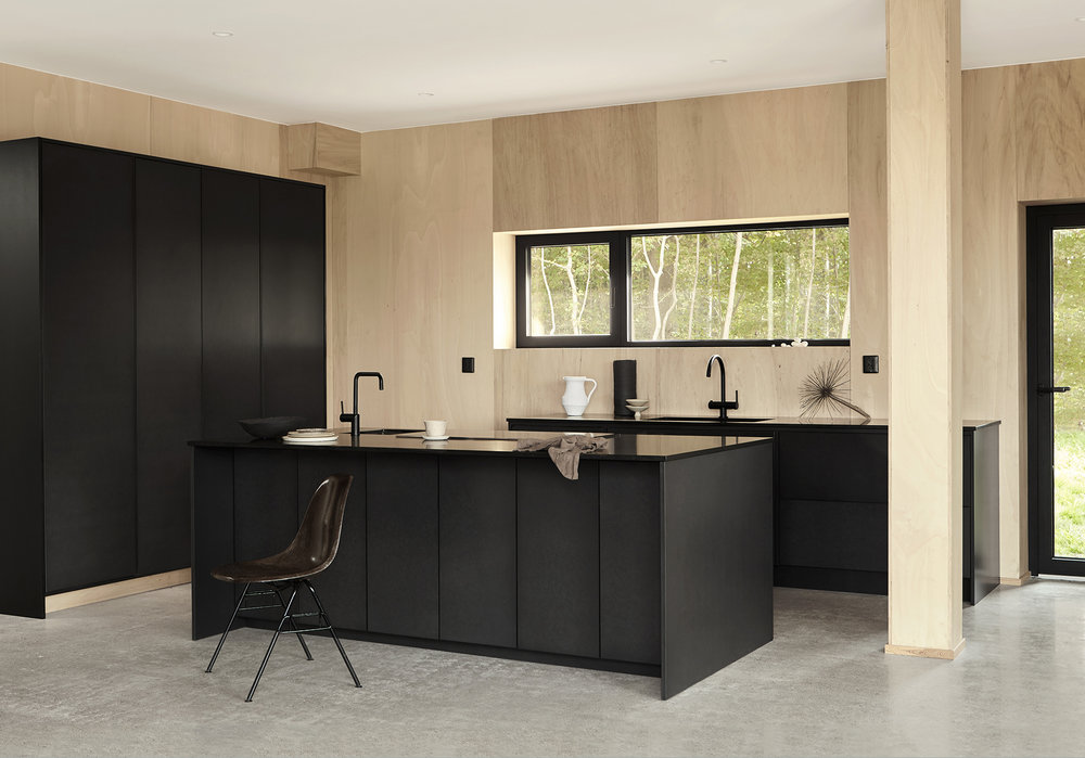 Together with the artist Emma Bernhard we have designed and built this black valchromat kitchen for her home. A black granite countertop and black details creates a contrast to the warm wooden tones. All together with the three kitchen sections creates a unique and minimalist kitchen layout.   Price on request     See more pictures