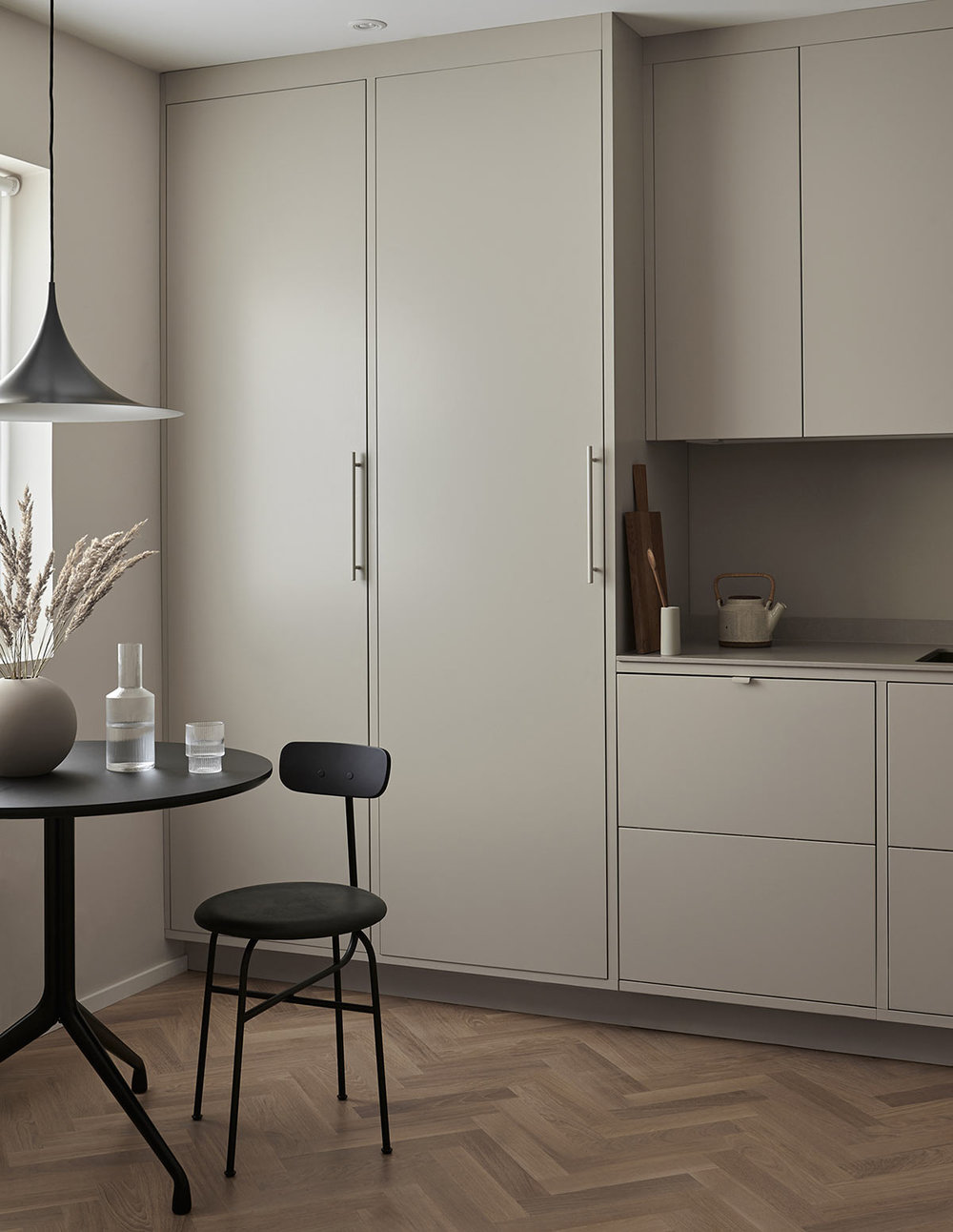 Grey kitchen with table, chairs and lamp from Frama, menu and gubi
