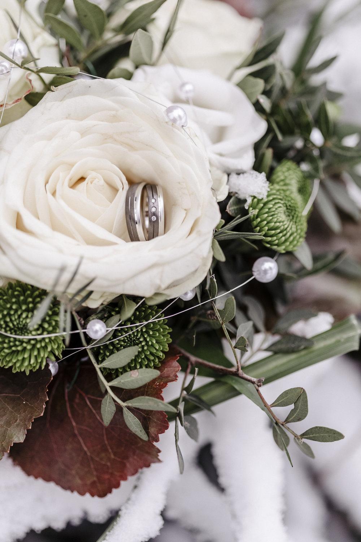 Der Brautstrauß mitsamt der Ringe im Schnee.