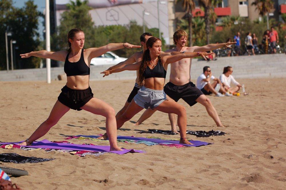 Voluntarios, miembros de #HE y personas sin hogar disfrutando de una sesión de yoga de la mano de  Leila.