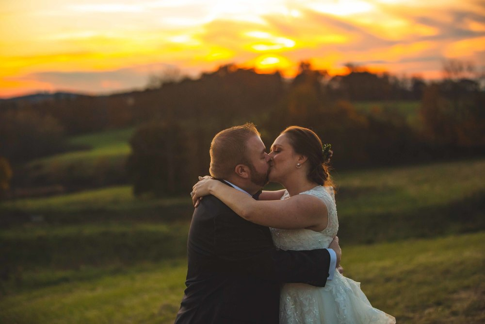 Bride and groom sunset kiss