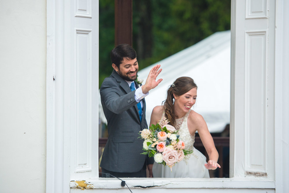 Bride and groom waving from window