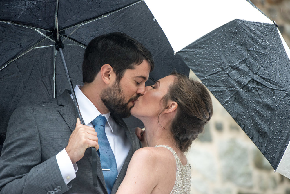 Bride and groom under umbrellas