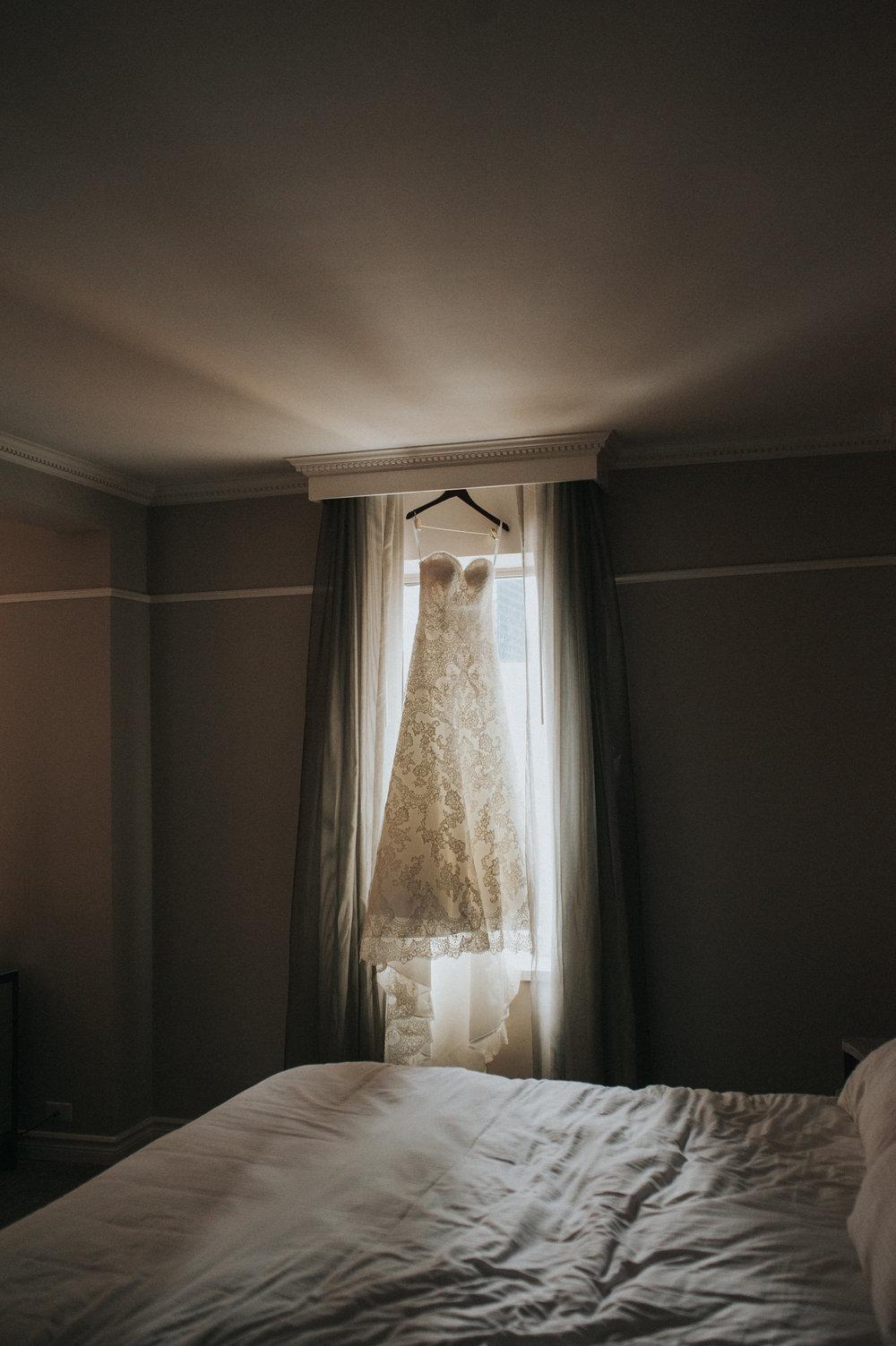 bride-wedding-dress-in-window-toronto-same-sex-wedding-willow-and-birch-photography-documentary-wedding-photographers.jpg
