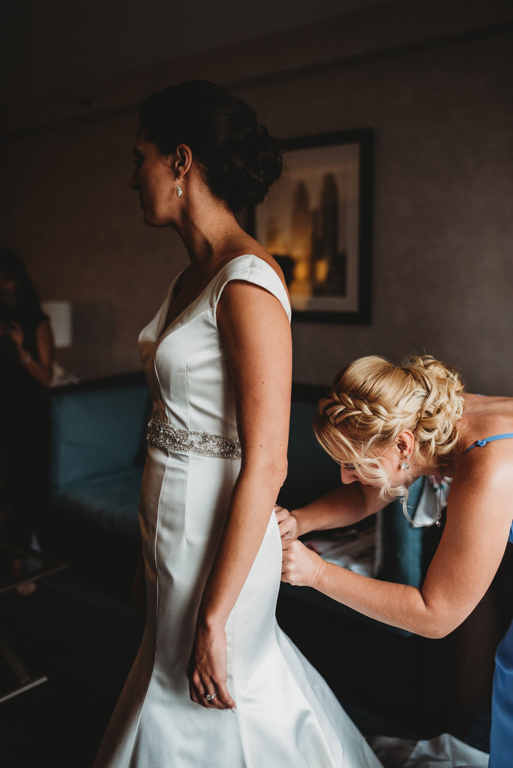 bride-getting-dress-on-getting-ready-pictures-eglington-grand-wedding-by-willow-birch-photo-toronto-documentary-wedding-photographers.jpg