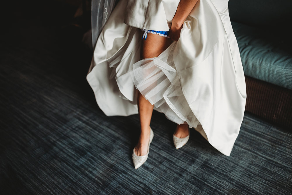 bride-putting-on-garter-getting-ready-photos-eglington-grand-wedding-by-willow-birch-photo-toronto-documentary-wedding-photographers.jpg