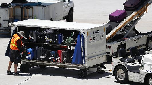 Getty Images  A Delta airlines worker is seen as luggage is loaded onto the plane at the Fort Lauderdale-Hollywood International Airport in Fort Lauderdale, Florida.