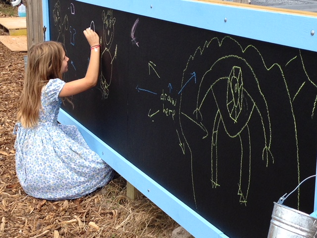 Mae Moore Bamburg plays with the new chalkboard at the grand opening of the new playground. Photo by Nick Terry.