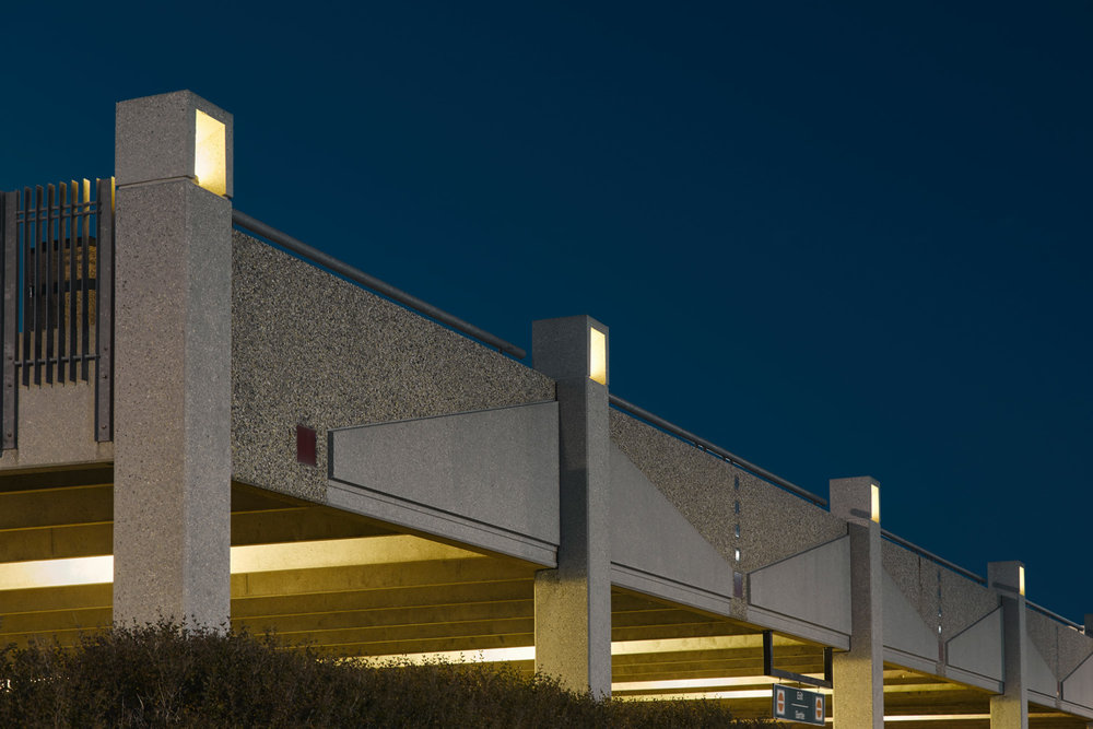 Wall panels of the precast concrete parking structure were developed with custom patterning in ceramic tile and coloured concrete to reflect the logo of the Winnipeg Airports Authority. The perimeter concrete lanterns, like classic Japanese stone lanterns, provide atmospheric lighting, complementing the character of the building.