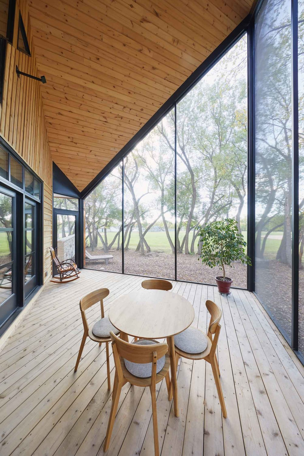 An airy porch overlooking a forested area encloses the end of one of the wings created by the cross-shaped design.