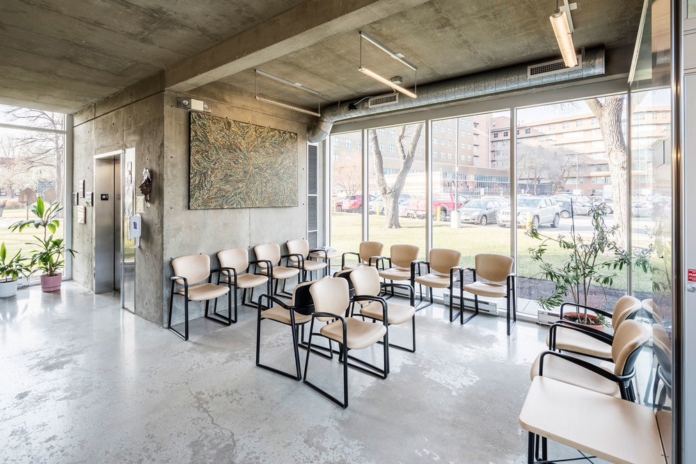 The main-floor waiting room is spacious and uncluttered, with views of the surrounding landscape. Seating, which is set aside the main corridor, occupies a space that suggests the scale of a living room.