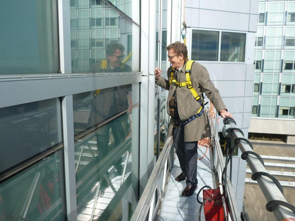 ….In a safety harness, architect Stephen Cohlmeyer examines wall components from a portable scaffolding. ..Équipé d'un harnais de sécurité, l'architecte Stephen Cohlmeyer examine les éléments d'un mur à partir d'un échafaudage portatif. ….