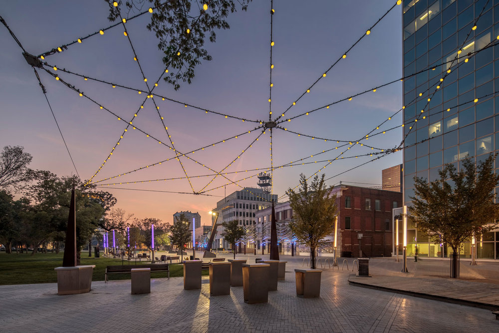 This plaza twinkles at night with multiple overhead LED lights. The space is a transitional connection between Victoria Park and the Scarth Street Mall, a well-used pedestrian street north of the plaza. Custom-made stainless steel tables were designed for casual lunches.