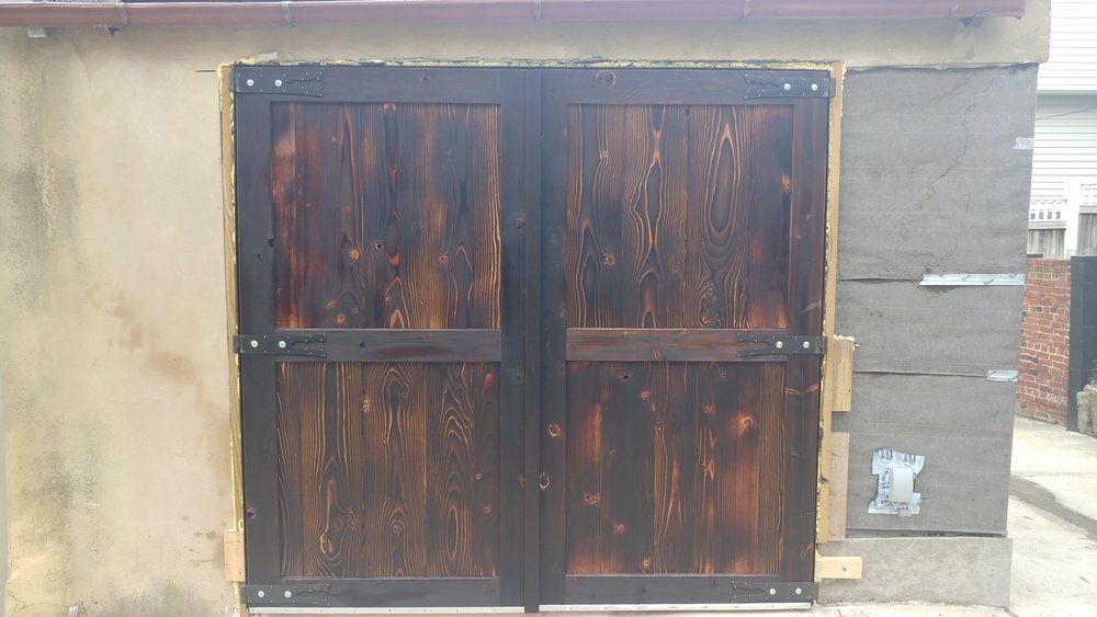 The doors have exteriors which have been charred then oiled. This process is a natural way to waterproof wood. The hinges were inspired by those on the gate to Himeji castle, Japan.