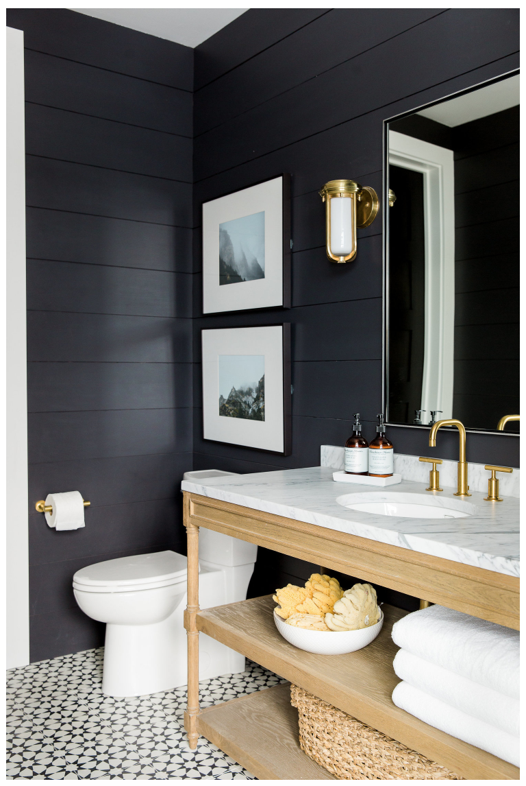 This vanity by  Studio McGee  is a perfect execution of open shelving in a bathroom to keep it lighter and more open, paired with a dynamic floor and dark moody walls.