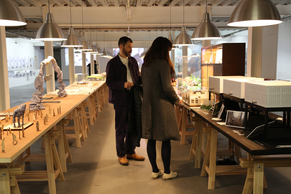 Eric Guibert and Ana Krec in front of the atelier's table at the ADAPT-r group exhibition, Ambika, London (photographer: Kate Heron)