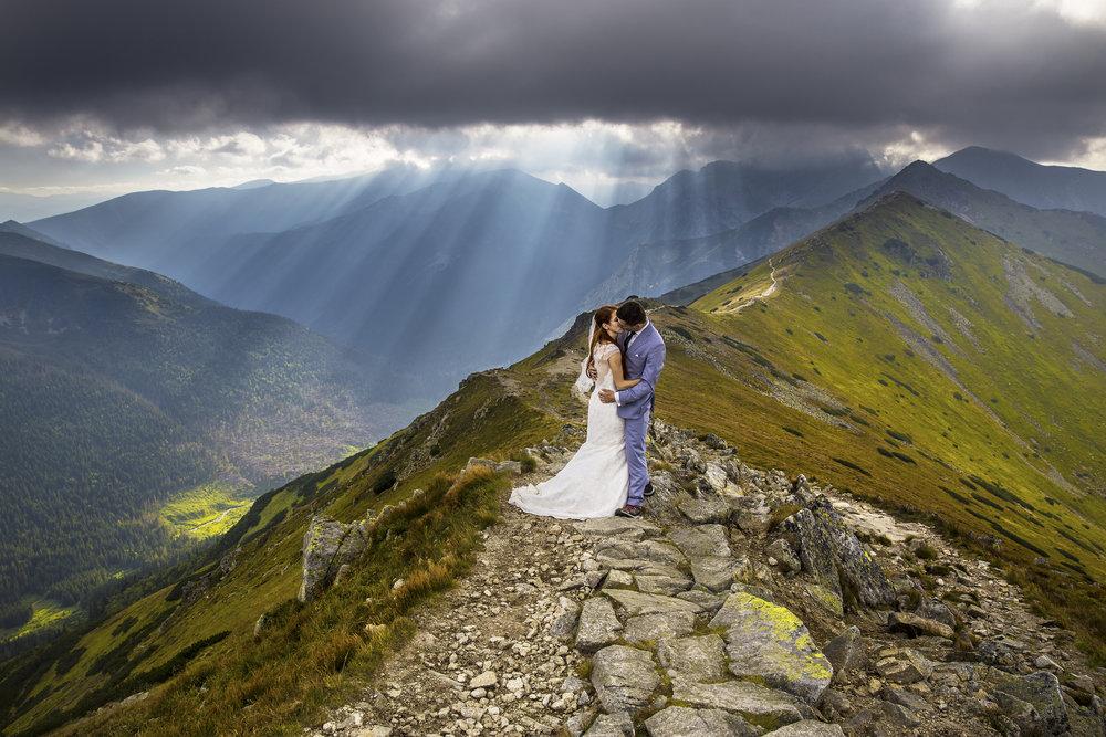 - Poznaliśmy się z Arkiem w górach, tam też po 2 latach znajomości dostałam od niego pierścionek zaręczynowy. Oczywistym więc było, że jedynym odpowiednim miejscem na naszą sesję ślubną będą góry i to te najpiękniejsze, czyli Tatry. Krzyśka znaleźliśmy przez portal tatromaniak.pl. Bardzo nam się spodobały jego prace, a gdy dowiedzieliśmy się, że robi sesje ślubne i ma wolny termin w sierpniu-nie mogliśmy nie skorzystać. Sesja na Kasprowym była dla nas fajną przygodą. Ogólnie raczej nie lubimy być fotografowani, ale praca z Krzyśkiem była przyjemna i naturalna, więc bardzo miło wspominamy ten dzień. Jedynym problemem było to, że całą sesje nie mogliśmy przestać się śmiać. Zdjęcia wyszły super, mamy wiele ciekawych ujęć, a nasz fotograf nie stracił pomysłowości nawet, gdy popsuła się nam pogoda. Wszystkim, którzy chcą mieć piękną pamiątkę na całe życie w najpiękniejszym miejscu na świecie - polecamy Krzysztofa!Magda i Arek