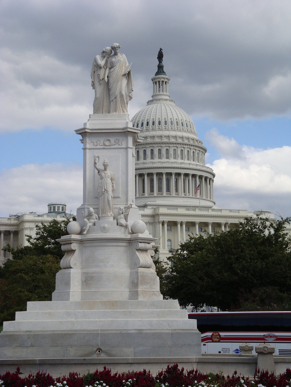 Statue of Grief (also known as America) weeping on the shoulder of History with the US Capitol dome in the background.