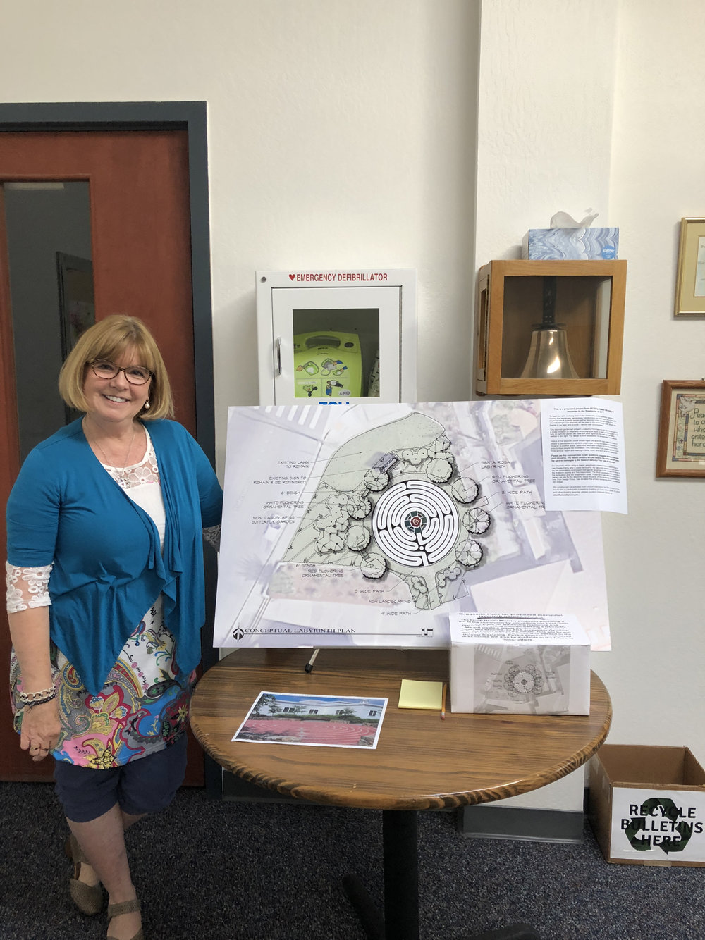 Pastor Cindy Alloway with plans drawn by landscaper Steve Kovanis of  Carlile-Macy