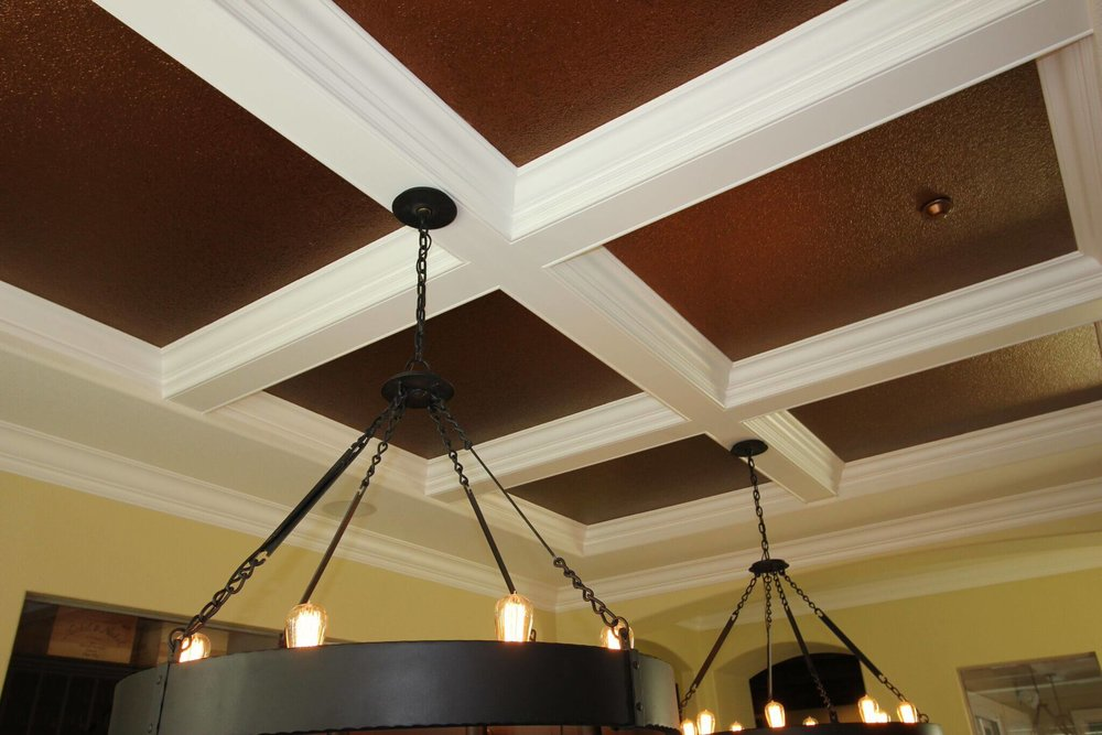 Copper metallic paint highlighting coffered trim detail in a dining room.