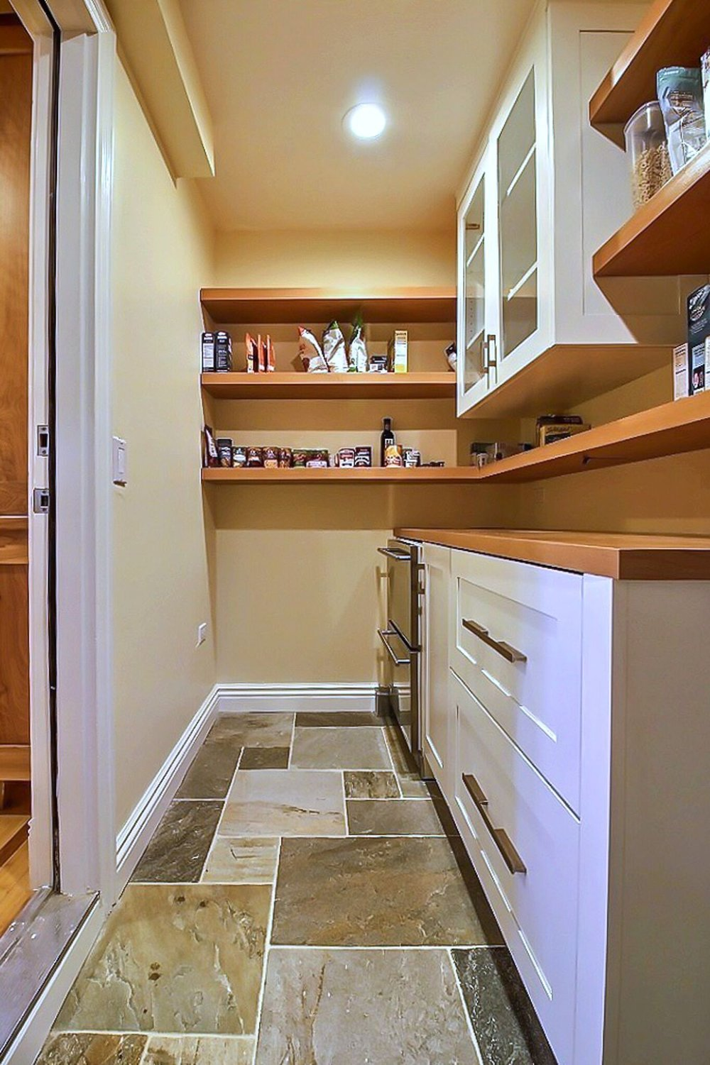 This pantry transitions from the garage with a slate floor.